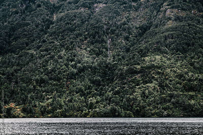 A lake underneath a steep mountainside by Justin Mullet for Stocksy United