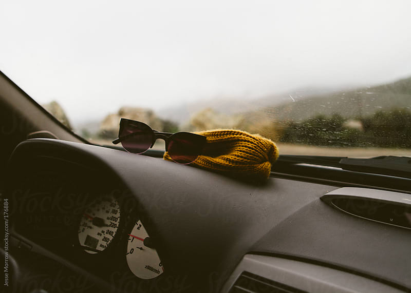 sunglasses and hat on dashboard of car by Jesse Morrow for Stocksy United