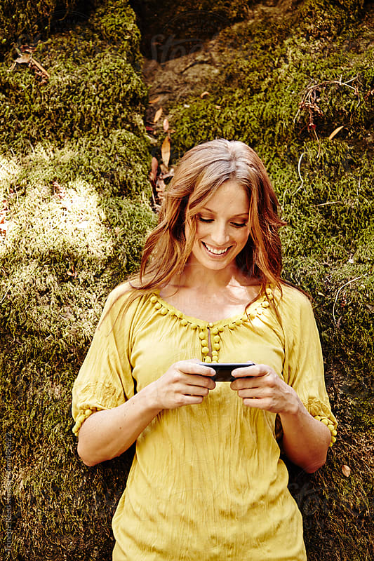 Beautiful redhead woman texting on cell phone in nature in California  by Trinette Reed for Stocksy United