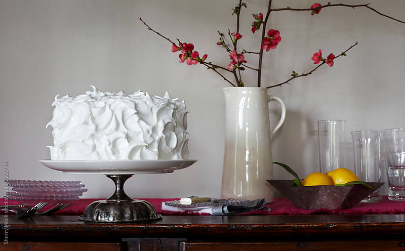 Fluffy white cake on buffet with serving dishes and utensils by Sherry Heck for Stocksy United