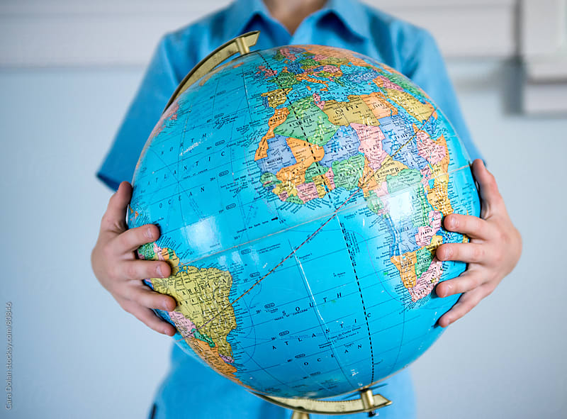 Boy holds a globe in his arms by Cara Dolan for Stocksy United
