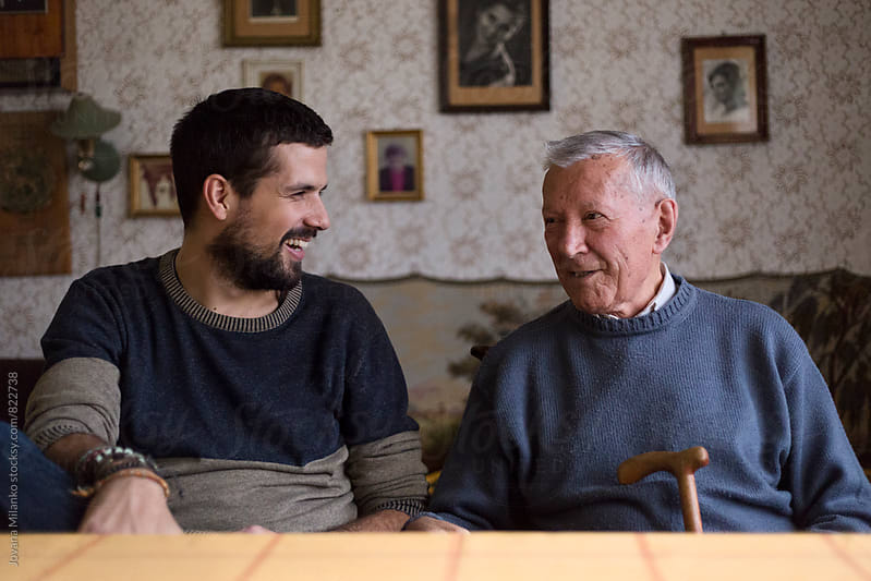 Grandpa and his adult grandson sitting at the table talking by Jovana Milanko for Stocksy United