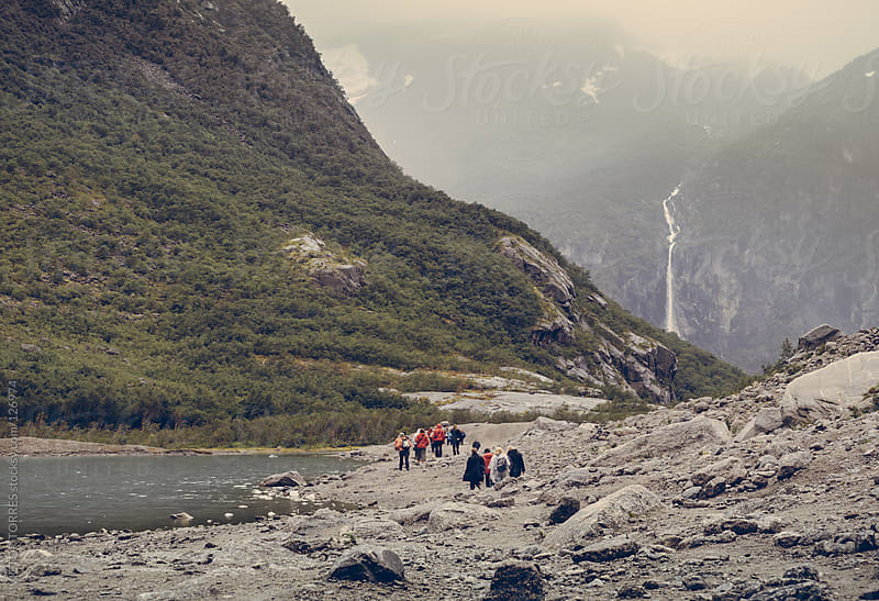 Group of people walking in Tunsbergdalsvatnet Lake by VICTOR TORRES for Stocksy United
