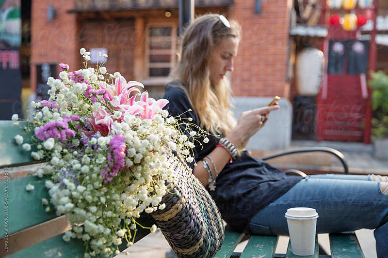 Beautiful woman looking at her phone while sitting outdoors by Jovo Jovanovic for Stocksy United