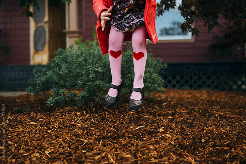 A Young Girl With Pink Tights Jumps in Her Front Yard by Amanda Voelker for Stocksy United