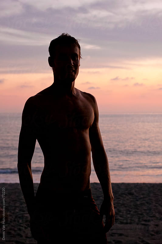 Silhouette of a healthy man standing on the beach in his board shorts  by Denni Van Huis for Stocksy United
