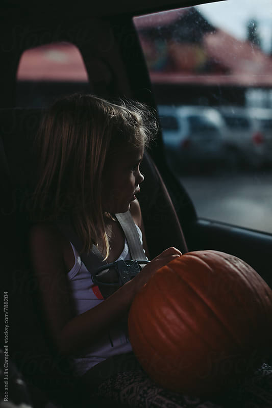 Little girl holding pumpkin in carseat by Rob and Julia Campbell for Stocksy United