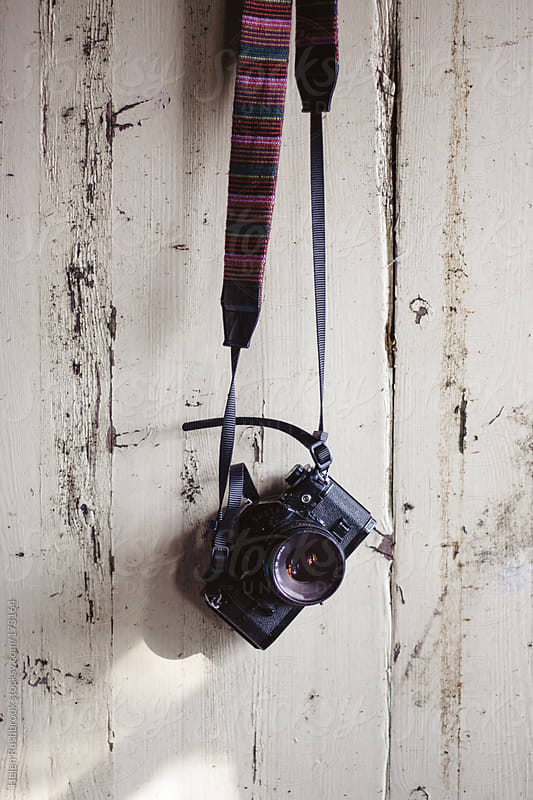 Vintage 35mm camera hanging on an old door by Helen Rushbrook for Stocksy United