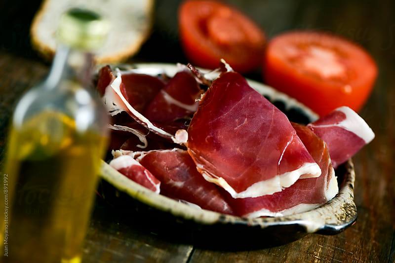 serrano ham, bread, olive oil and tomato by juan moyano for Stocksy United