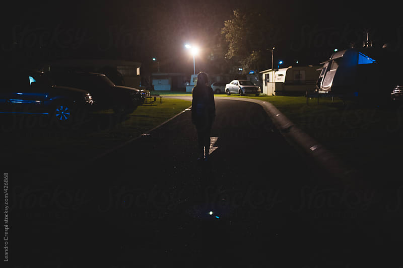Woman walking on a camping during night by Leandro Crespi for Stocksy United