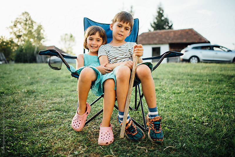 Brother and sister having fun outside, sitting on the same chair by Boris Jovanovic for Stocksy United