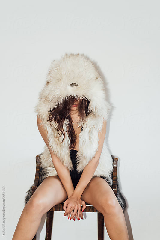 Young woman hiding behind the fur by Kate & Mary for Stocksy United