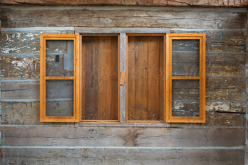 Windows in a log cabin with shutters closed by David Smart for Stocksy United