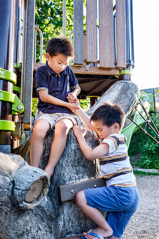 Asian kids helping each other in the playground by Suprijono Suharjoto for Stocksy United