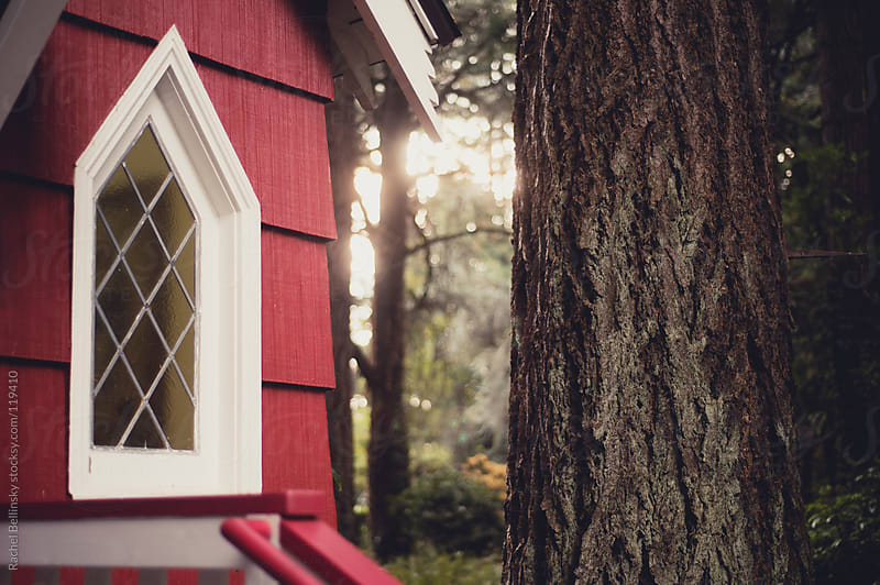 Leaded diamond window of red storybook house in the woods by Rachel Bellinsky for Stocksy United