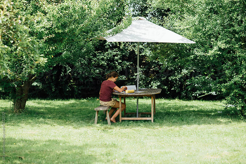 young woman sitting under umbrella in her yard by Léa Jones for Stocksy United