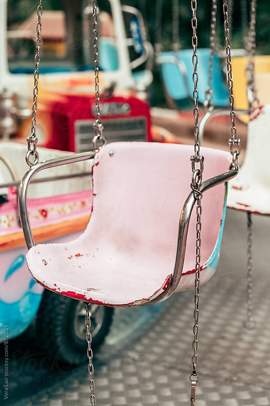 Pink metal carousel chair in amusement park by Vera Lair for Stocksy United