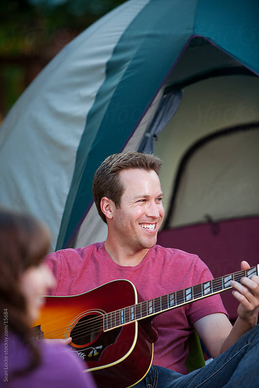 Camping: Guy Plays Guitar By Tent by Sean Locke for Stocksy United