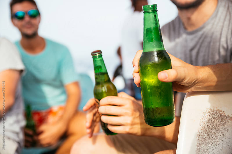 Front view of male hands holding green beer bottles outdoors on a sunny day by Alejandro Moreno de Carlos for Stocksy United