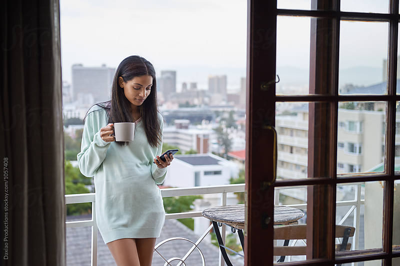 beautiful young woman with coffee and phone outdoors  on the balcony by Daxiao Productions for Stocksy United