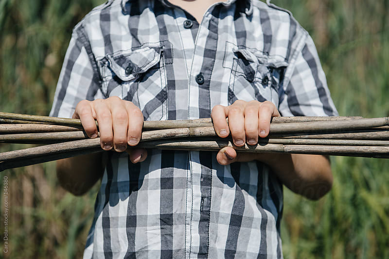 Boy holds a collection of sticks by Cara Dolan for Stocksy United