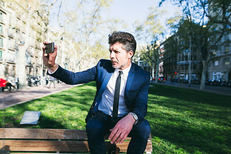 Mature businessman taking a photo sitting on a bench. by BONNINSTUDIO for Stocksy United