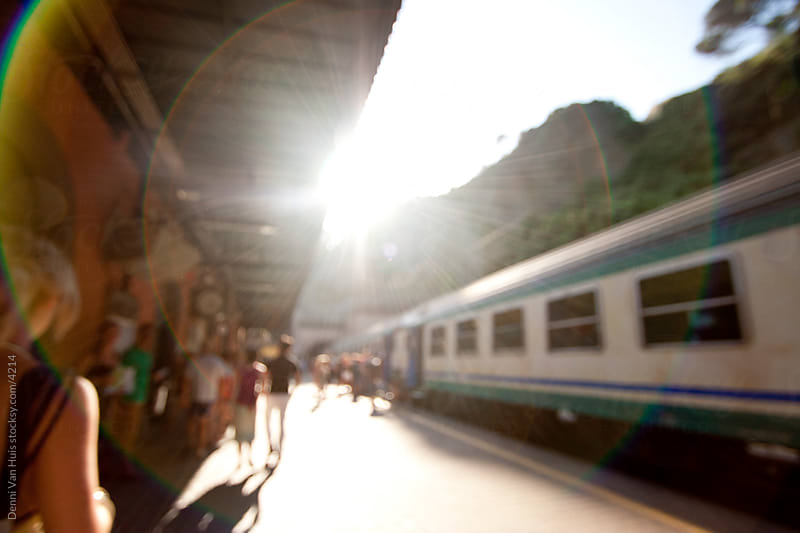 Train at a train station in Italy with people standing around. by Denni Van Huis for Stocksy United