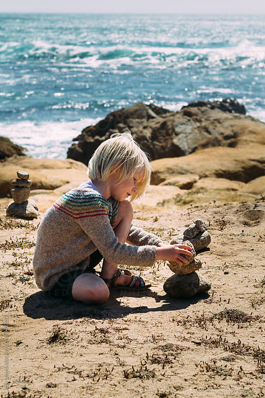 girl building a cairn next to the ocean by Jess Lewis for Stocksy United