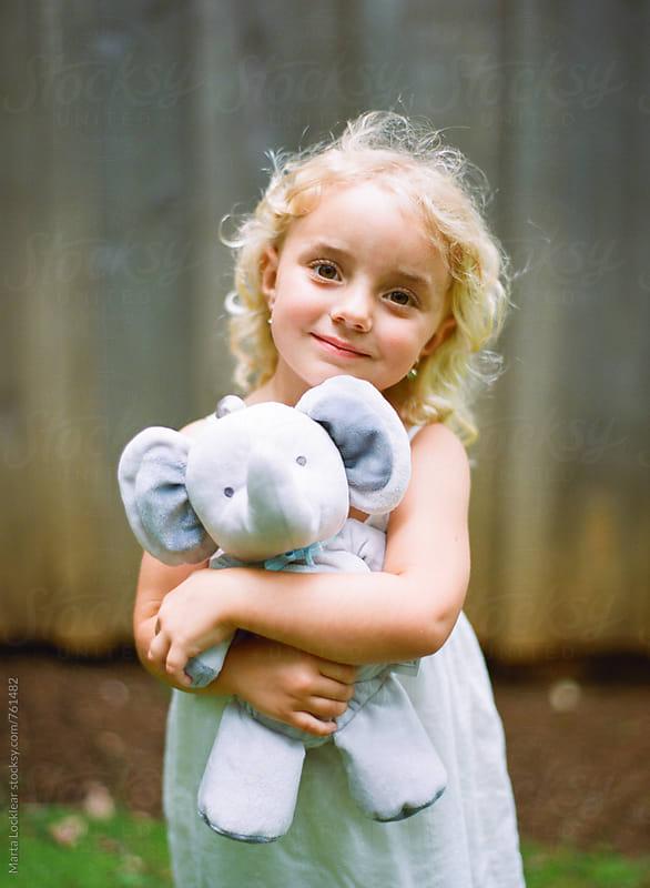 Little girl hugging a toy elephant by Marta Locklear for Stocksy United