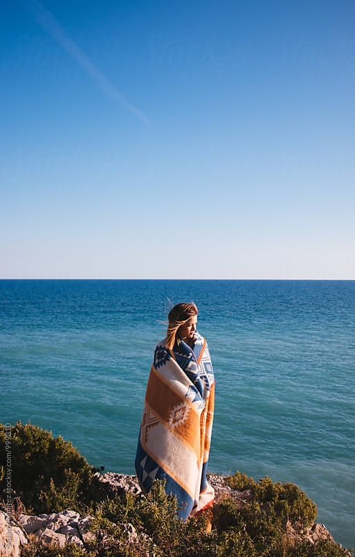 Young woman on a cliff, covering her with a blanket by Susana Ramírez for Stocksy United