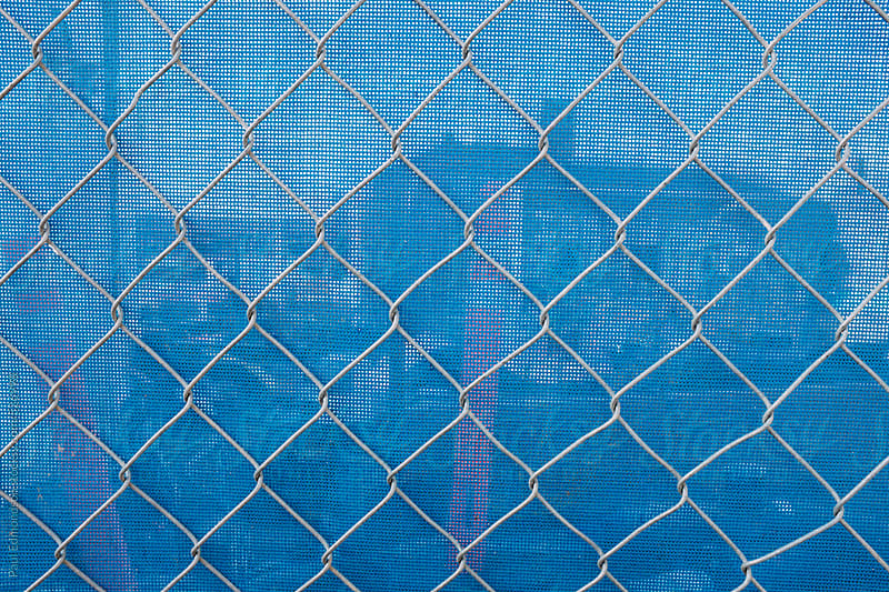 Chain-link fence in front of blue plastic tarp at construction site by Paul Edmondson for Stocksy United