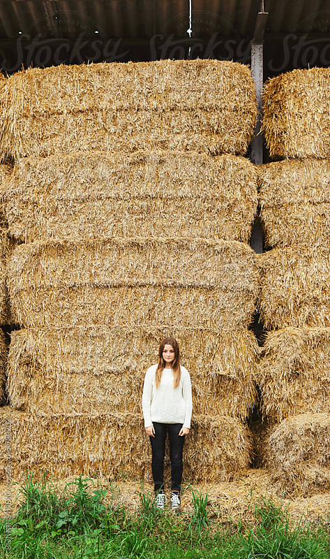 Teen girl standing in front of a haystacks on a farm. by BONNINSTUDIO for Stocksy United