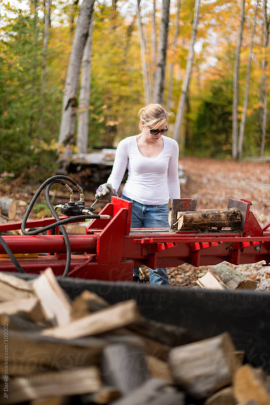 Woman Splitting Wood for Winter Firewood In Autumn at Cottage by JP Danko for Stocksy United
