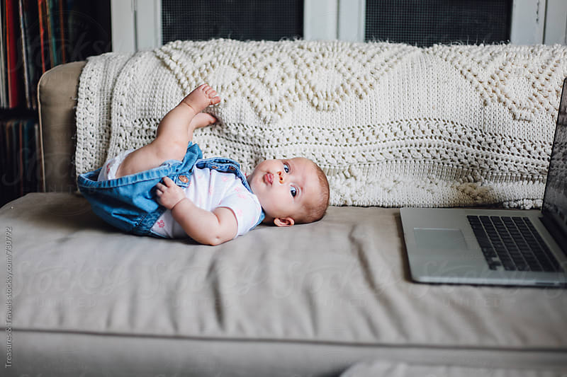 Cute Baby sitting beside a computer by Treasures & Travels for Stocksy United