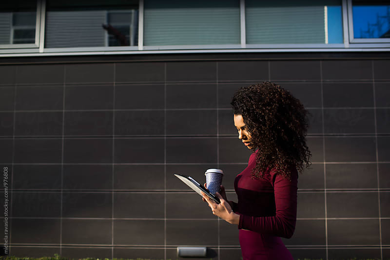 Attractive brunette using digital tablet in front of a black wall by michela ravasio for Stocksy United