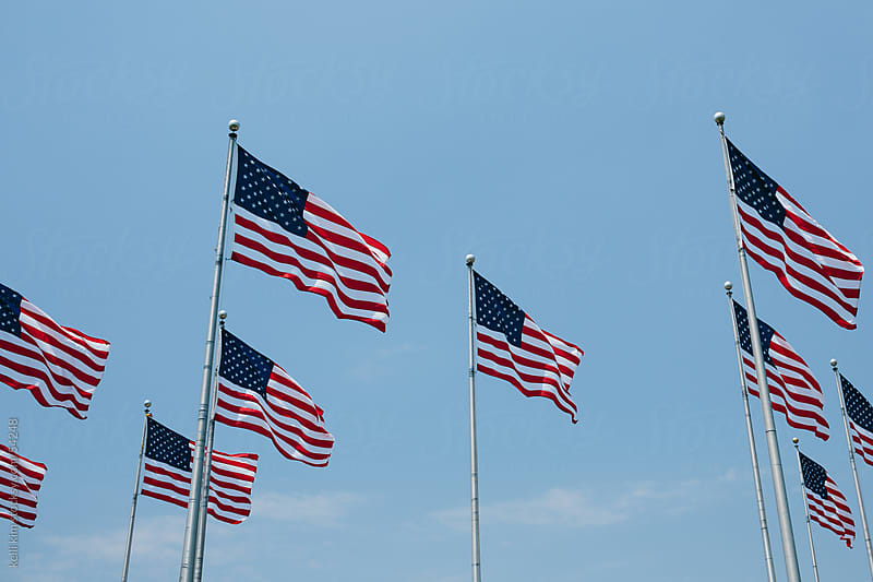 American Flags Blow In Wind Against Blue Sky by Kelli Seeger Kim for Stocksy United