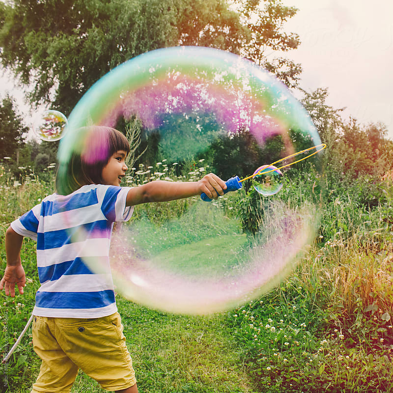 Cute little boy creating huge bubble from a bubble wand in the nature by Nabi Tang for Stocksy United