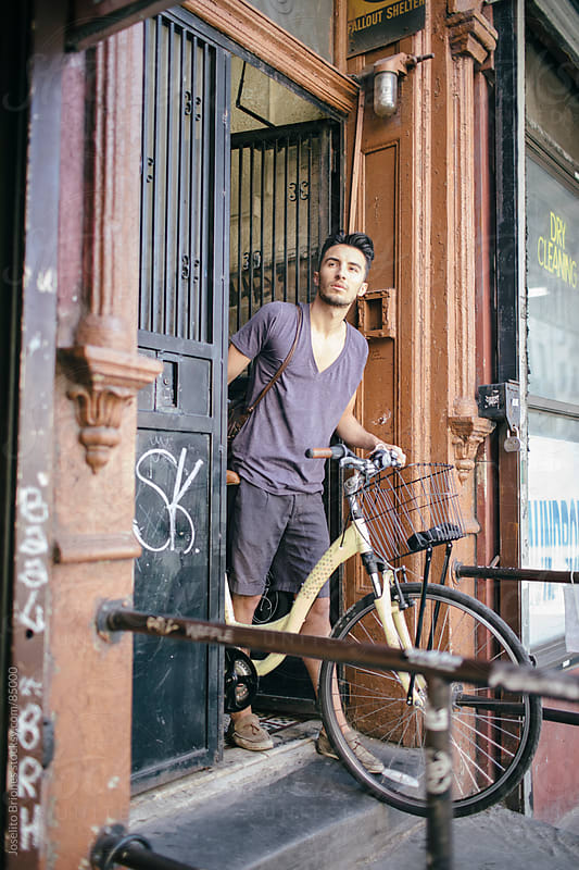 Casual Young Man Leaving New York Apartment in Bicycle by Joselito Briones for Stocksy United