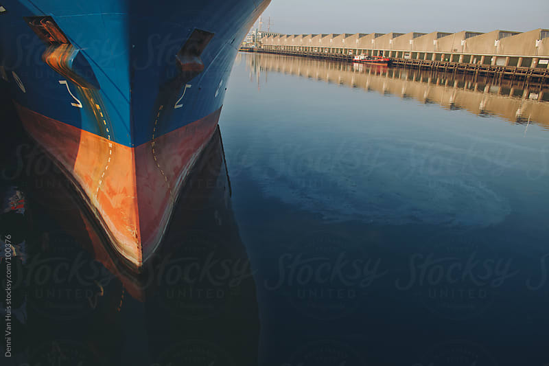 polluted water next to the front of a ship by Denni Van Huis for Stocksy United