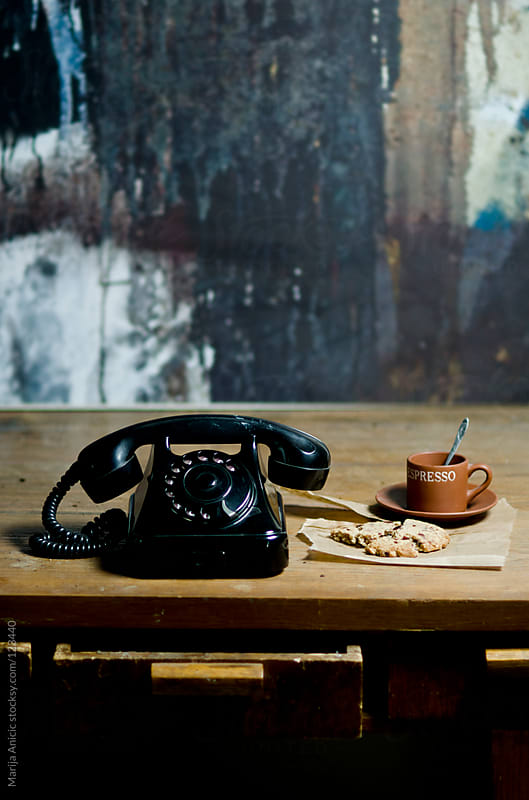 Old vintage black telephone with cookie and cup of coffee by Marija Anicic for Stocksy United