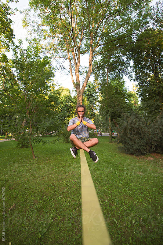 Young man sitting in lotus position on slackline by RG&B Images for Stocksy United