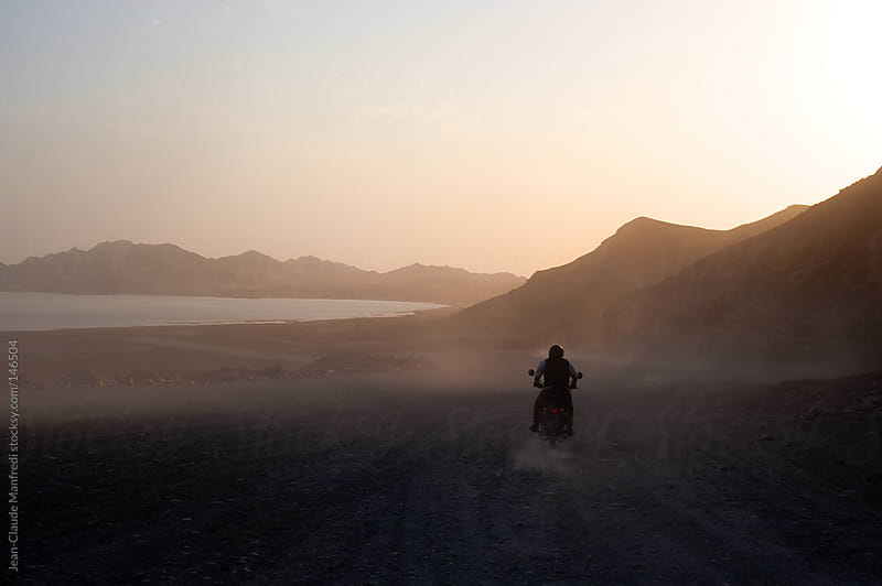 Motorcyclist rides his bike on a dirt and wild road at sunset towards the Caspian Sea by Jean-Claude Manfredi for Stocksy United