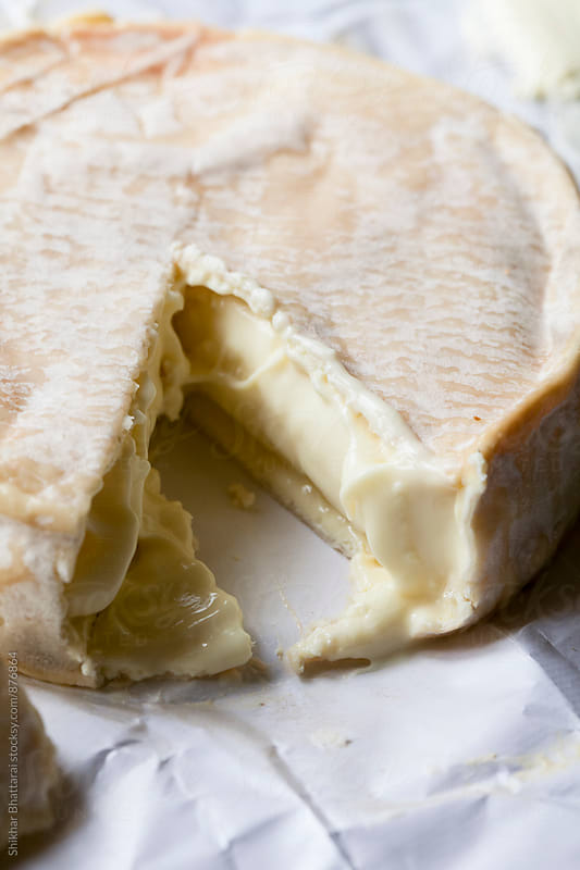 Gooey inside of camembert after a slice is taken out. by Shikhar Bhattarai for Stocksy United