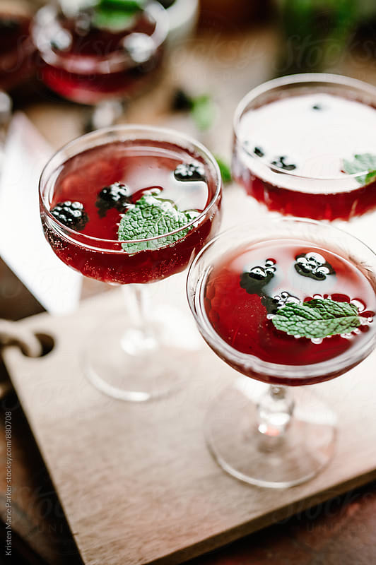 Blackberry gin cocktail with mint in crystal coupe glass by Kristen Marie Parker for Stocksy United