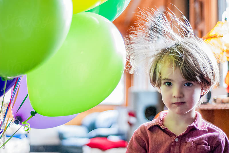 Birthday balloons make boy's hair stand on end by Cara Dolan for Stocksy United