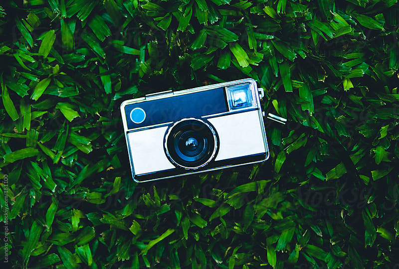 old vintage camera over grass by Leandro Crespi for Stocksy United