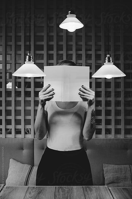 woman hiding her face with a book by Thais Ramos Varela for Stocksy United