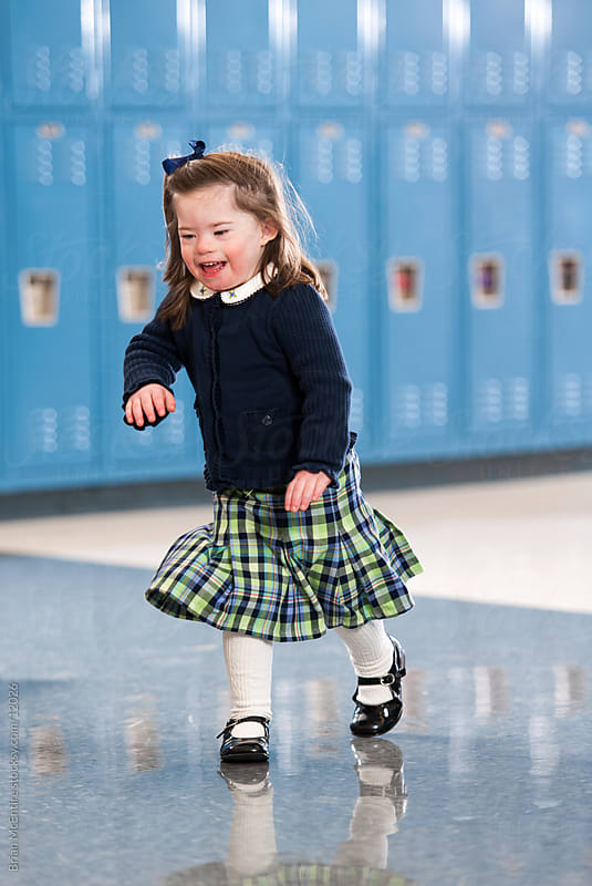 Kindergarten Girl with Down Syndrome Running Through School Halls by Brian McEntire for Stocksy United