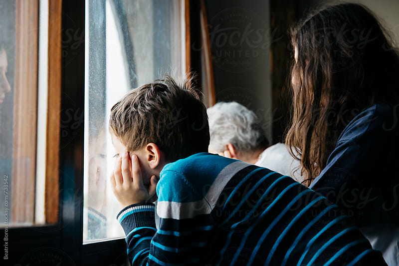Boy and his family by the window waiting for something to happen by Beatrix Boros for Stocksy United