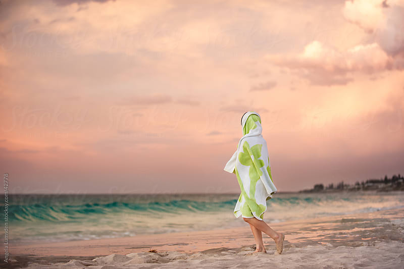 Child wrapped in a towel at the beach watching a stormy sunset by Angela Lumsden for Stocksy United